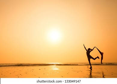 dancing woman at sunset on the beach