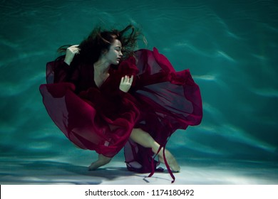 Dancing woman under the water in a pool in a red dress.