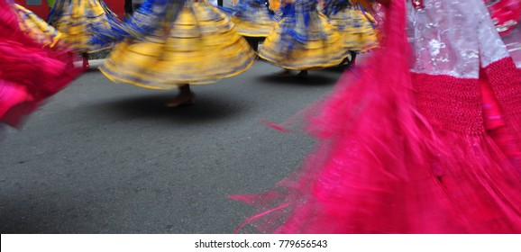 Dancing women in colorful dresses in carnaval