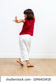 dancing young child showing one's back and fingers to count with relaxed body language and bare feet, wooden floor and white background