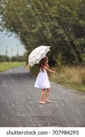 Dancing young girl in summer rain