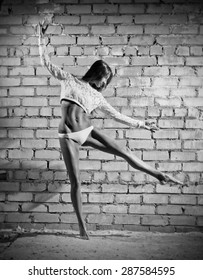 Dancing young woman on grey wall (monochrome version)