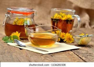 Dandelion jam in glass, herbal tea, spoon, dandelion head around, small colander and full jar of jam in background