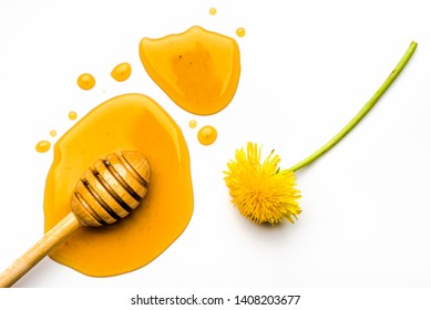 Dandelion yellow honey drop and stick with honey on white background.