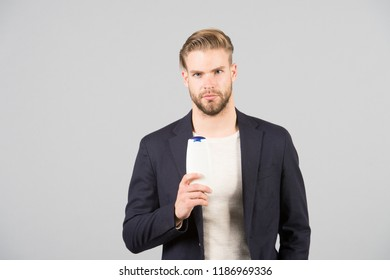 Dandruff common male problem. Remedies get rid of dandruff. Man formal suit hold bottle shampoo grey background. Itchy scalp and flakiness skin. Shampoo solve dandruff problem. Anti dandruff shampoo.