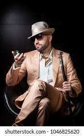 Dandy man dressed as mafia boss, pimp or playboy looks at himself in the pocket mirror, wearing sunglasses, white hat and pink or peach suit, sitting in a leather chair, isolated on black background