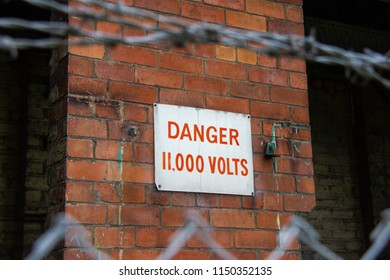 Danger 11,000 volts sign on brick wall