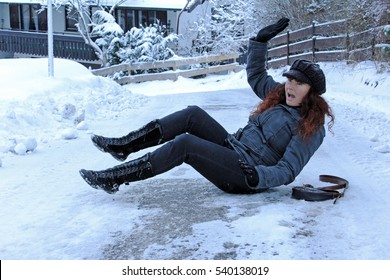 Danger of accidents on snowy roads. A woman has slipped on the street