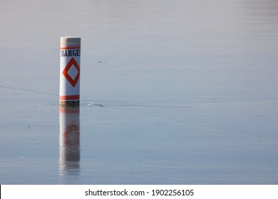 Danger buoy locked in ice.  Reflection of marker in the ice.  Blue sky reflected in the cracked ice.  Winter scene with a warning flotation device.
