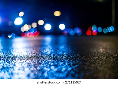 Danger of the city at night, the cars driving on the road and shine the headlights. View from the level of asphalt, in blue tones