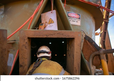 Danger confined space sign defocused  certified trained worker wearing helmet PPE work uniform working as spotter stand by rescue at entry and exit confined space manhole gas test detector permit book