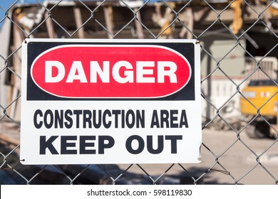 Danger Construction Area sign on a chain link fence in front of a building demolition