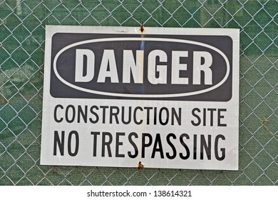 danger, construction site, no trespassing as warning message on metal grid wall