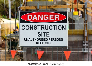 A 'Danger, Construction site, Unauthorised Persons Keep Out' sign mounted on a wire fence in front of a building site