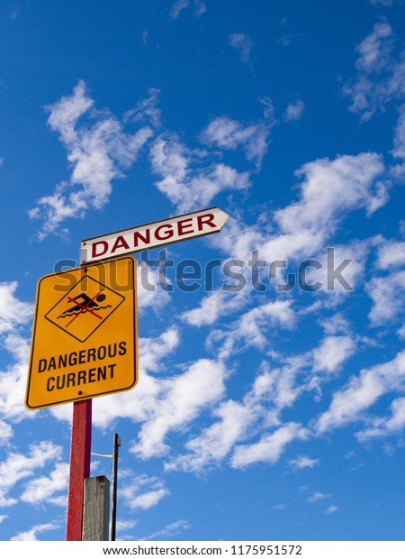 Danger, dangerous current beach signage against bright blue cloud flecked sky.