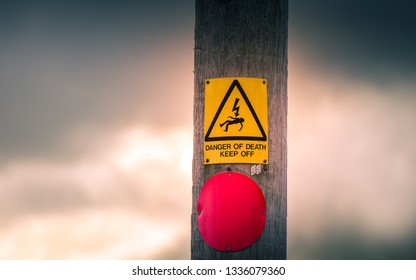 Danger of Death due to electrocution warning sign attached to a weathered wooden electricity pylon. Dark storm clouds can be seen in the background.