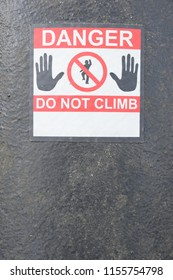 DANGER DO NOT CLIMB red and white warning sign with symbol of man climbing and two hands on black background with shallow depth of field.