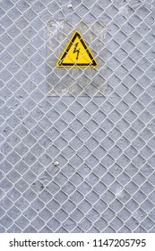 Danger of electrocution yellow sign on gray background with metal wire fence. High voltage warning sign. Electric bolt in yellow triangle safety symbol: caution, risk of electric shock.