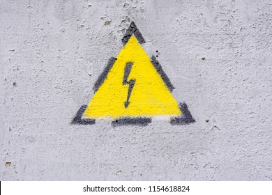 Danger of electrocution yellow sign on gray painted wall. High voltage warning sign. Electric bolt in yellow triangle safety symbol: caution, risk of electric shock.