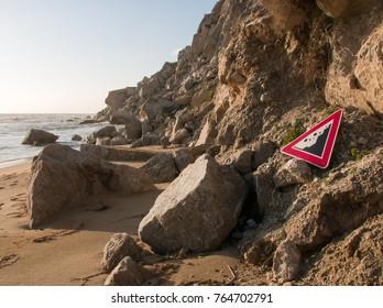 Danger falling rocks sign between falling rocks at the Beach of Marina Siculiana, Provincia Agrigento, Sicily, Italy