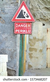 Danger falling rocks triangle sign in English and in Maltese language
