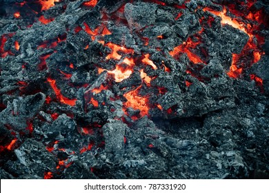 Danger, hazard, energy concept. Lava flame on black ash background. Formation, geology, nature, environment. Magma textured molten rock surface.