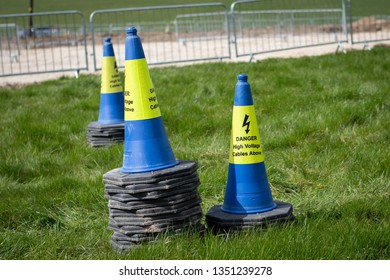 Danger high voltage cables above road blue and yellow traffic cones stacked on grass in front of railings
