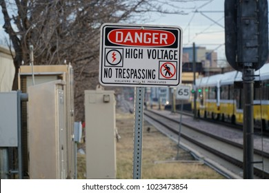 Danger, High Voltage, No Trespassing sign  warns people to stay clear of area along train tracks in the City of Richardson Tx.