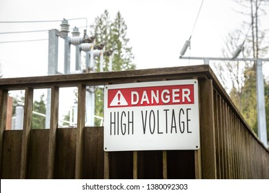 """""""Danger.  High Voltage"""" sign at a electrical substation, with electrical transformers in the background"""