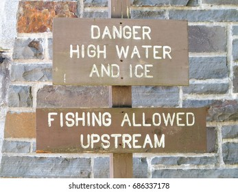 Danger high water and ice sign and fishing allowed upstream sign