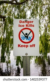 Danger ice kills keep off sign post on the bank of a small lake