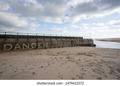 Danger keep off. Coastal Drowning hazard. Sea wall Gorleston UK. Warning sign at Gorleston-on-sea public beach near Great Yarmouth Norfolk.