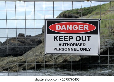'Danger Keep Out Authorised Personnel Only' sign board on fence gate at construction site. In Australia workplace safety sign has rocks and water in background
