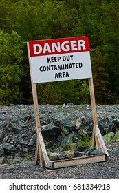 A danger keep out of contaminated area sign on rocky ground.