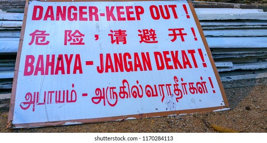 """Danger Keep out sign board in English Chinese Malay and Tamil on white background with red wordings on the ground at a construction site.  Translation : """"Danger Keep Out""""."""