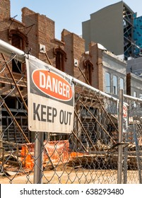 Danger Keep Out sign on a chain link fence in front of a dilapidated, run-down building in vertical format.