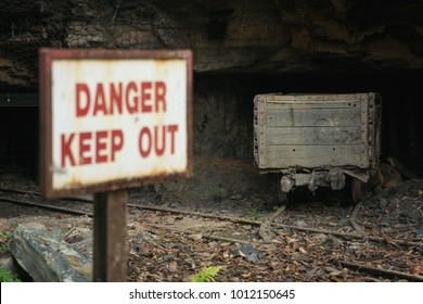 Danger Keep Out Warning Sign at the entrance of mining cave with rails and mine trolley