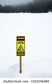 """""""Danger. Lake Not Monitored. Ski Area Boundary"""" sign along a frozen lake covered in winter snow, with space for text on top"""