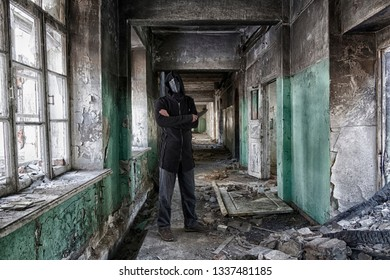 Danger maniac with knife in hand, in leather mask of lague doctor and hood, inside old abandoned house. Scary movie scene