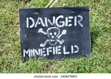 Danger minefield, black sign with white skull and crossbones on a grass, closeup