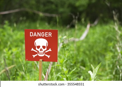 Danger of mines or toxic poison sign on a field