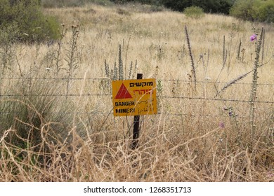 Danger mines! yellow warning sign and barbed wire fence of a minefield in the Israeli Golan Heights by the border with Syria