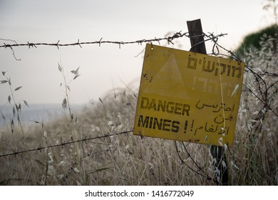 Danger mines - yellow warning sign next to a mine field, close to the border with Syria, in the Golan Heights, Israel.