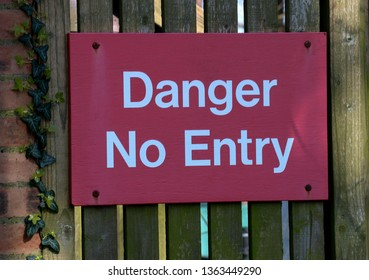 Danger No Entry signboard on an old perimeter wall gate