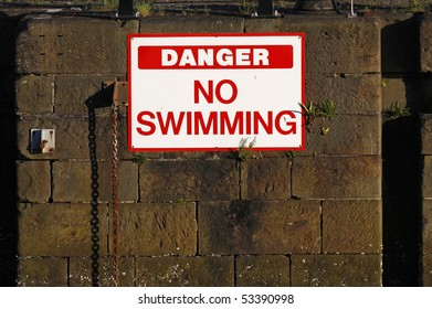 Danger no swimming sign in a marina