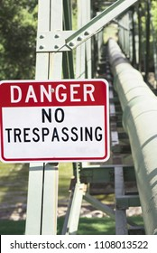 Danger, no trespassing sign. Bright red posted sign warning to keep up industrial pipeline.