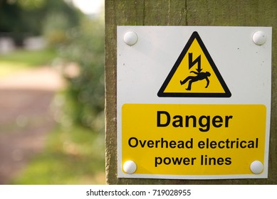 Danger overhead electrical power lines warning sign on wooden post with out of focus background