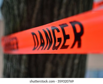 Danger Red Tape Warning in front of a tree/ Red Danger sign Tape