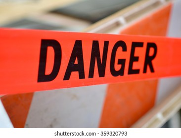 Danger Red Tape Warning in front of a orange and white safety gate/ Red Danger sign Tape