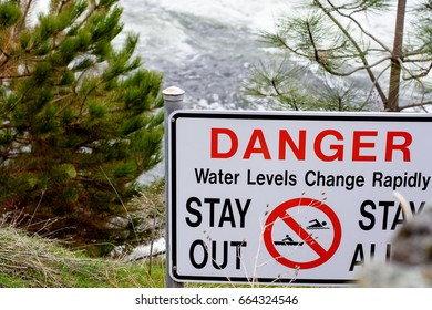 Danger sign along the shore of a fast moving river